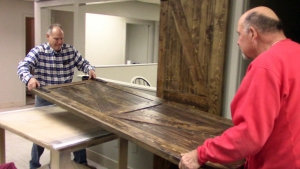 Lifting heavy barn door from authentic barn wood for display in showroom
